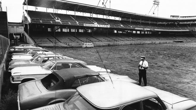 Cars impounded by the Cincinnati Police Department park on the grass of Crosley Field in 1971 as an officer takes inventory.