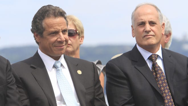 From left, Gov. Andrew Cuomo and aide to Gov. Cuomo Larry Schwartz sit on a podium during an event about Tappan Zee Bridge funding in 2012.