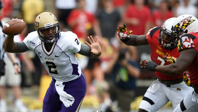 James Madison quarterback Vad Lee (2) is pursued by Maryland linebacker Yannick Ngakoue (7) and Quinton Jefferson, right, during the first half of an NCAA college football game, Saturday, Aug. 30, 2014, in College Park, Md. (AP Photo/Nick Wass)