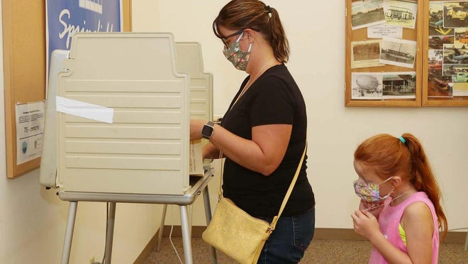 Meaghan Soohey votes Tuesday, Aug. 4, 2020, on the Springfield school levy while her daughter Scarlette Soohey, 6, a pupil at Spring Hill Elementary School, waits behind her at the Springfield Township Administration Building.
