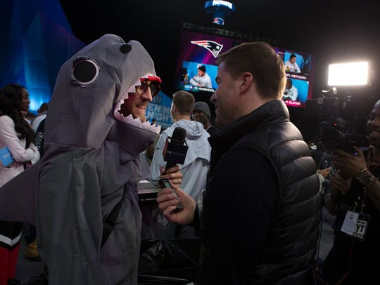 A journalist in a shark costume is interviewed during