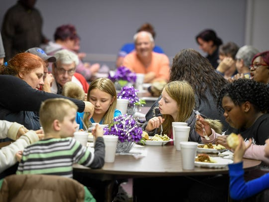 Families eat dinner at the East End Community Table Feeding Program held at Henderson's Bennett Memorial United Methodist Church Thursday. The program started by Larry and Kathy Holt has nearly tripled since it began in May of last year and needs more churches to come on board to help with the food, February 15, 2018.