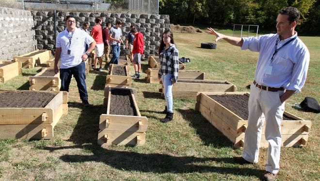 Advisor Kevin Sullivan gives a tour of the Middletown High School South environmental club's new student-run garden, which will produce food for a local food bank.