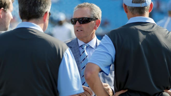 North Carolina athletic director Bubba Cunningham, center, talks to men on the sidelines before an NCAA college football game against South Carolina in Charlotte, N.C., Thursday, Sept. 3, 2015. (AP Photo/Chuck Burton)