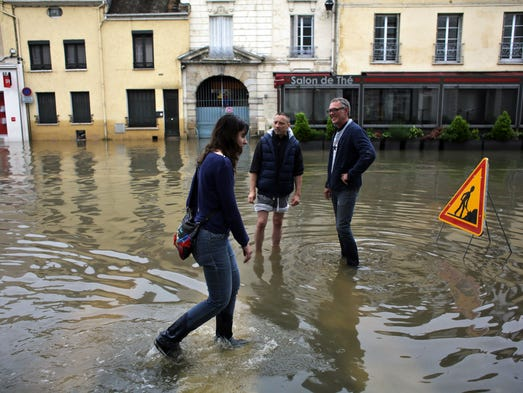 People go about their business along a flooded street