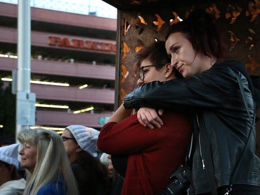 Belma Zigic, in back, hugs Rosie Gully during a vigil