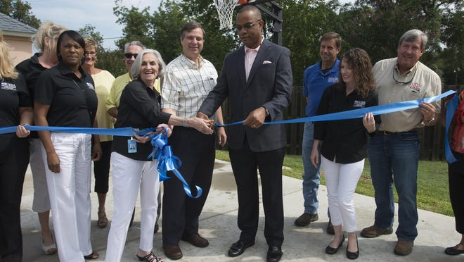 Home Builders Assoc. of West Florida Auxiliary Council and Lakeview Center board members dedicate a new $15,000 basketball court and play area at the Meridian of Lakeview Center facility Friday morning.
