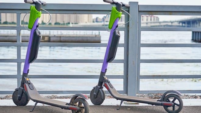 Two electric scooters parked, facing the river in a city.