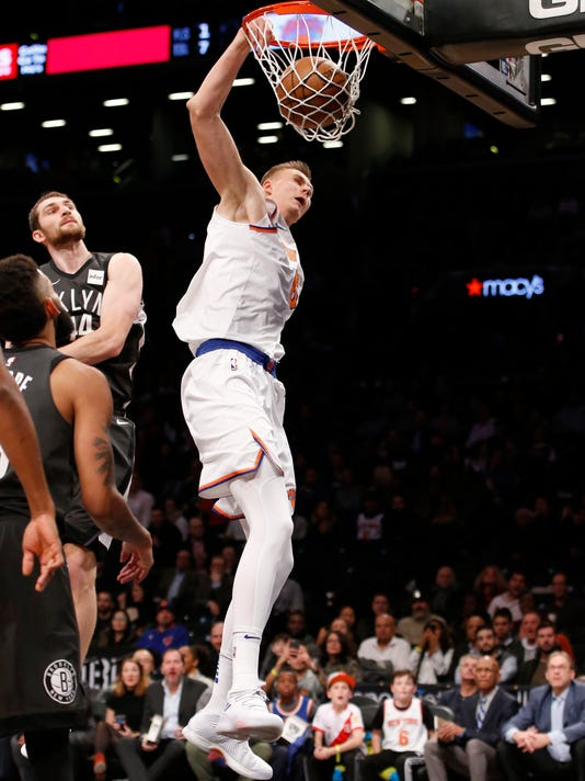 New York Knicks forward Kristaps Porzingis (6) dunks in front of Brooklyn Nets center Tyler Zeller (44) in the first half of an NBA basketball game, Thursday, Dec. 14, 2017, in New York. (AP Photo/Kathy Willens)