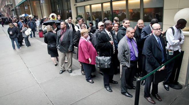 Job seekers wait in line to see employers at a National Career Fairs job fair in New York.