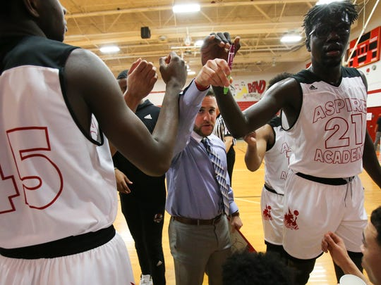 Aspire Academy head coach Jeremy Kipness, center, gathers his players after instructing them during their game against Orangeville Prep at Seneca High School.   Feb. 9, 2018