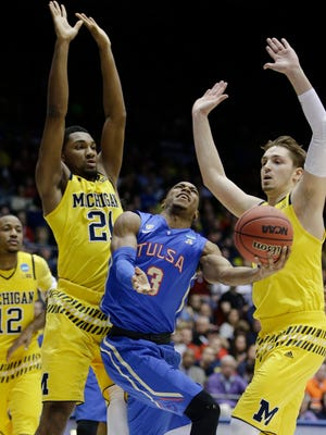 Tulsa's Shaquille Harrison (3) shoots against Michigan's Zak Irvin (21) and Mark Donnal, right, during the first half of U-M's win in the NCAA tournament First Four round in Dayton, Ohio, Wednesday.