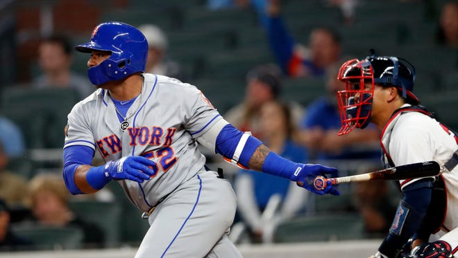 New York Mets' Yoenis Cespedes (52) drives in the go-ahead run with a single in front of Atlanta Braves catcher Kurt Suzuki during the 12th inning of a baseball game Friday, April 20, 2018, in Atlanta. New York won 5-3 in 12 innings.