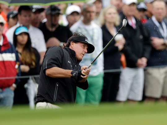 Phil Mickelson hits a chip shot on the 10th hole during the first round of the Valero Texas Open golf tournament, Thursday, March 27, 2014, in San Antonio. Play was delayed for more than two hours Thursday due to rain and fog. (AP Photo/Eric Gay)
