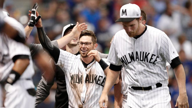 Brewers second baseman Eric Sogard celebrates after scoring the winning run.
