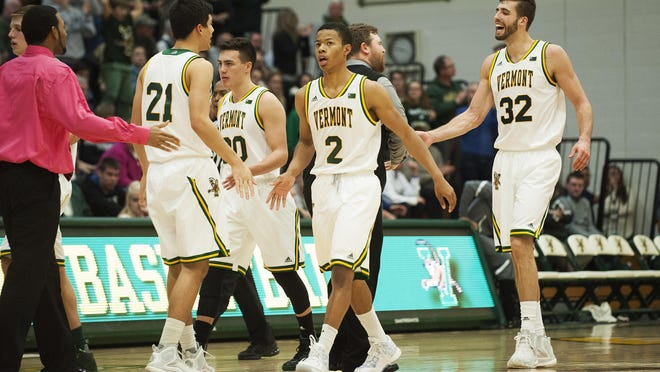 Trae Bell-Haynes (2) and Ethan O'Day (32) head to the bench with teammates for a timeout during the men's basketball game between Siena and Vermont earlier this season.