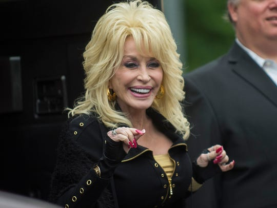 Dolly Parton smiles and waves to fans as she steps