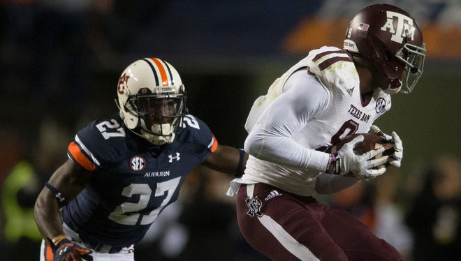 Auburn defensive back Robenson Therezie (27) goes to tackle Texas A&M wide receiver Ricky Seals-Jones (9) during the NCAA football game between Auburn and Texas A&M on Saturday, Nov. 8, 2014, in Auburn, Ala. Texas A&M defeated Auburn 41-28 after Auburn fumbled twice on there last two drives.
