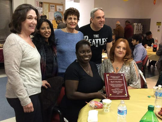 Ruth Mathieu (center, seated) is surrounded by members