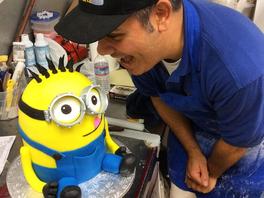 Baker Roman Blas pictured with a custom cake.