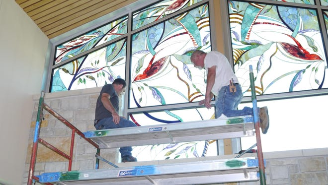 James Simpson, left, and Tracy Zech of TC Glass install stained-glass panels at Holy Spirit Catholic Parish.