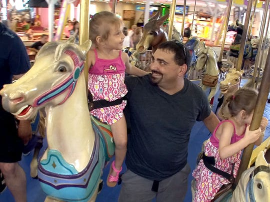 Doug Snell, Toms River, rides the Casino Pier carousel Monday, July 21, 2014, in Seaside Heights, NJ, with his daughters Avery (left), 2, and Madison, 4.    There is a plan to auction off the carousel.    SEASIDE HEIGHTS, NJ  ASB 0722 SEASIDE CAROUSEL   CAROUSEL0721C    STAFF PHOTO BY THOMAS P. COSTELLO / ASBURY PARK PRESS
