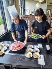 Seung Choi Jang, left, chef and owner of Mi Dahm, and manager and wife Eun Sun Park prepare a full-course meal at their Korean restaurant in Upper Tumon on April 30.