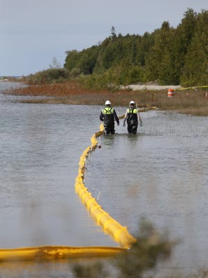 Enbridge workers walk along the shoreline checking a section of boom used in shoreline cleanup assessment techniques during the Enbridge emergency response exercise at the Straits of Mackinac on Thursday, Sept. 24, 2015.