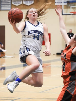Redwood's McKenzie Darnell, left, goes up for a layup over Selma's Rachel Vierira during Thursday's Central Section Division II high school girls basketball quarterfinal game.
