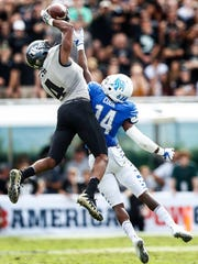 Memphis defender Jonathan Cook (right) can not stop UCF receiver Tre'Quan Smith (left) from making a catch during second quarter action of the the AAC Championship football game in Orlando, Fl., Saturday, December 2, 2017.