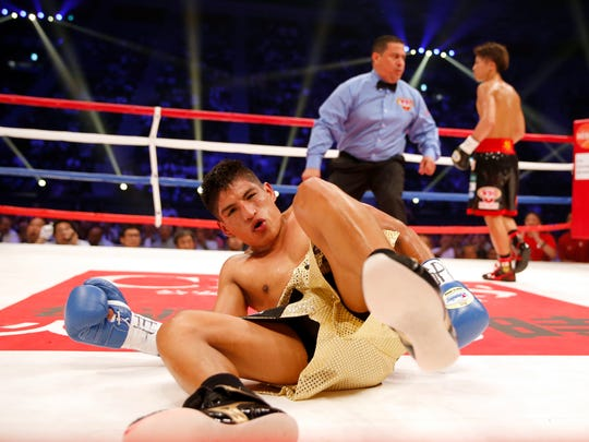 Ricardo Rodriguez of the U.S. lies on the mat after being knocked down by Japanese champion Naoya Inoue, right, in the third round of their WBO super flyweight boxing world title match in Tokyo, Sunday, May 21, 2017. Inoue knocked out Rodriguez in the round. (AP Photo/Toru Takahashi)