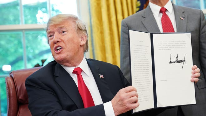 Watched by Vice President Mike Pence, President Donald Trump shows an executive order on immigration which he just signed in the Oval Office of the White House on June 20, 2018 in Washington.