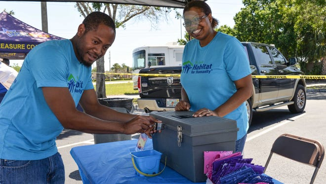 """St. Lucie County Habitat for Humanity volunteers Chantay Lacaze and Kervans Joseph play the """"find the key that opens the toolbox"""" activity on April 28."""
