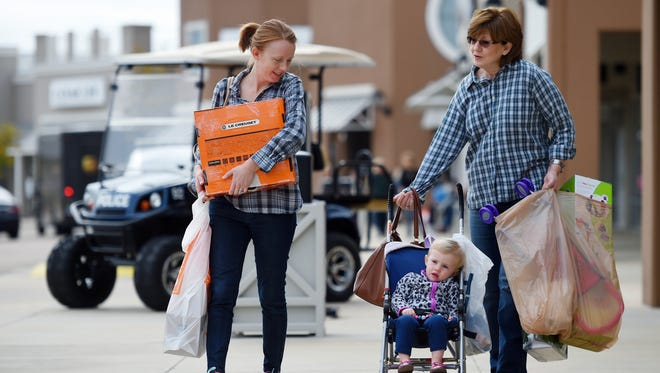Stephanie Tompkins, left, her mother, Sandy Hall, and Stephanie's daughter, Amelia,  all of Brandon, head to their vehicle carrying merchandise while taking advantage of Black Friday deals  at the Outlets of Mississippi in Pearl.