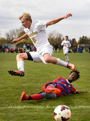 St. Cloud Cathedral's Jake Minkkinen jumps over St. Cloud Apollo's Kader Abdi to avoid colliding as they try to keep the ball inbounds during the first period Saturday, Oct. 14, at Whitney Field.