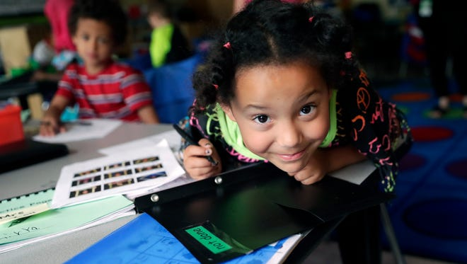Fort Howard Elementary School kindergartener Dezirea Razo smiles while finishing some class work on June 6 in Green Bay.