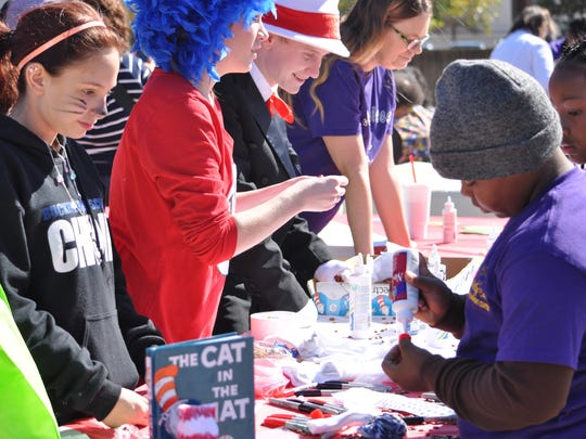 (From left) Katrina Paul helps Jamail Franklin make a Cat in the Hat sock puppet Saturday at the United Way of Central Louisiana's Seasons Readings.