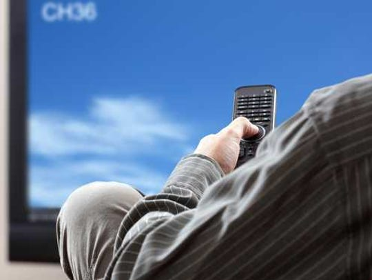 A man sitting in front of TV with remote in hand.