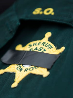 An East Baton Rouge Sheriff's deputy wear black tape over his badge July 18, 2016 at a makeshift memorial at the site of a shooting that left three policemen killed and three wounded in Baton Rouge July 17.