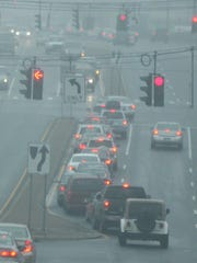 Motorists move slowly through a thick fog that fell