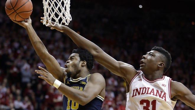 Michigan's Derrick Walton Jr. drives against Indiana's Thomas Bryant during the first half.
