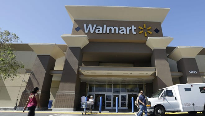 Customers walk outside of a Wal-Mart store in San Jose, Calif.