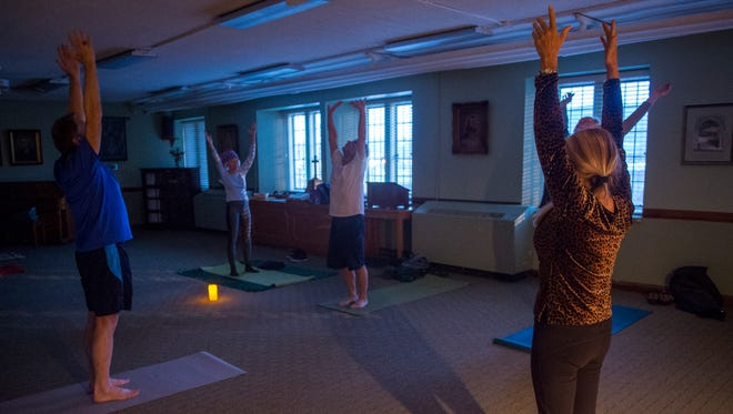 Yoga poses are practiced during an evening yoga class held at Church Street United Methodist on Monday, March 13, 2017, in downtown Knoxville .
