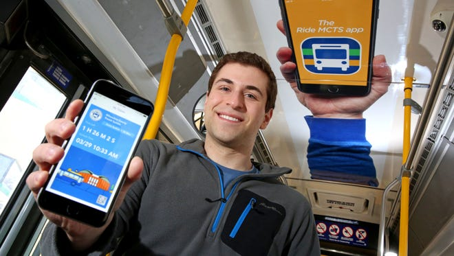 Aaron Redlich, co-founder of Tixora LLC, shows the Milwaukee County Transit System's Ride MCTS mobile ticketing and trip planning app beneath an ad for the app on the ceiling of an MCTS bus.