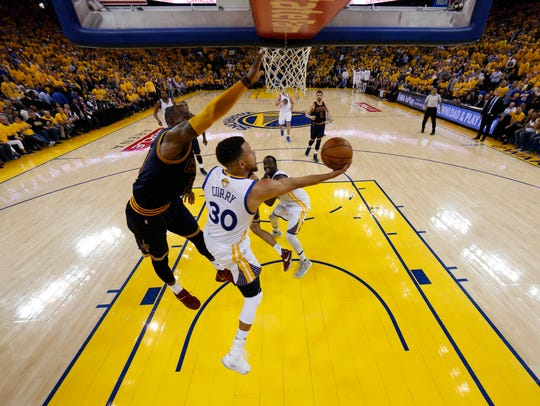 Stephen Curry shoots past LeBron James during Game