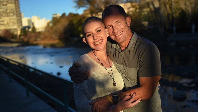 Haley Carroll and her dad Kevin pose for a portrait along side the Truckee River in Reno on Nov. 21, 2015. Both Haley and her dad, who is the principal of Sparks High School are eager to return back to school.