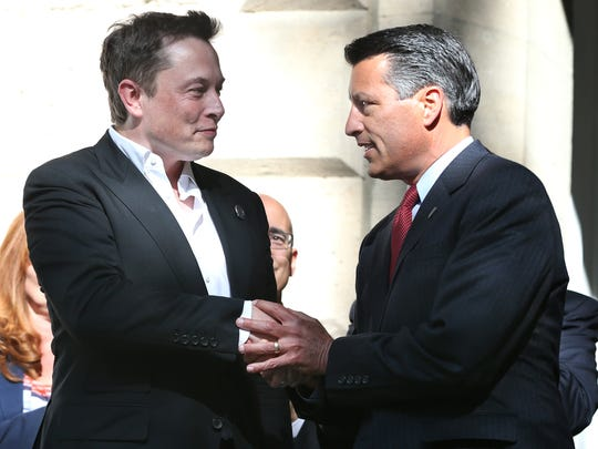 "Tesla Motors CEO Elon Musk, left, and Nevada Gov. Brian Sandoval shake hands following a press conference in Carson City on Sept. 4, 2014, where it was announced Tesla would build its $5-billion battery ""gigafactory"" in Nevada."