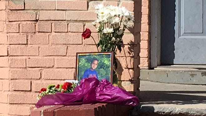 A photo of Dariel Sosa, 9, and flowers at a makeshift memorial on a front porch Friday in Perth Amboy. Dariel died Thursday after falling when a deck rail gave way.