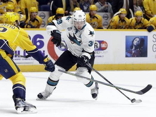 Sharks center Logan Couture (39) passes the puck around