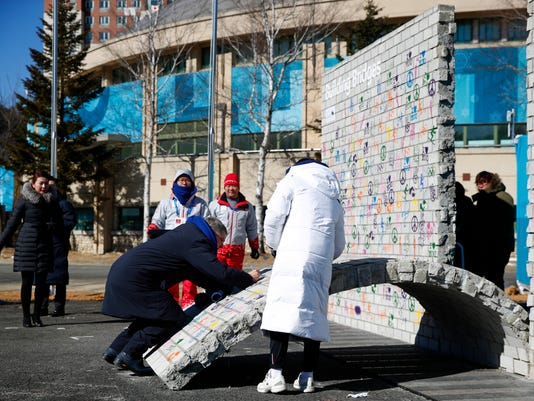 International Olympic Committee President Thomas Bach signs the Olympic Truce mural during a ceremony inside the Pyeongchang Olympic Village prior to the 2018 Winter Olympics in Pyeongchang, South Korea, Monday, Feb. 5, 2018. (AP Photo/Patrick Semansky, Pool)